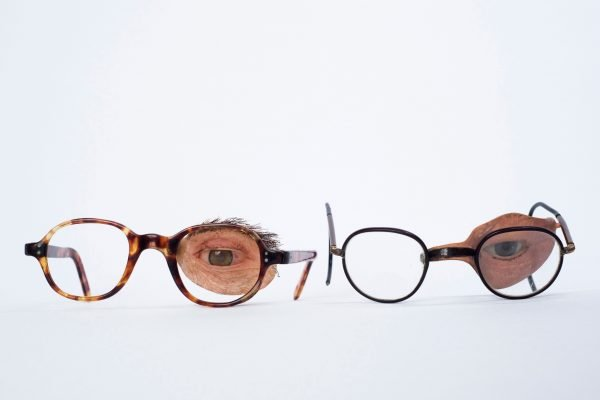 two pairs of spectacles with prosthetic eyes attached