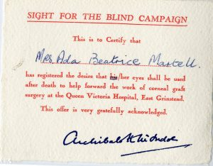 A typed card, which has red writing on it. It was created for the Sight for the Blind Campaign and is signed by Sir Archibald McIndoe