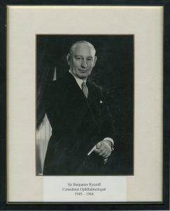 A framed black and white photograph of Sir Benjamin Rycroft, an older gentleman in a dark suit with his hands crossed