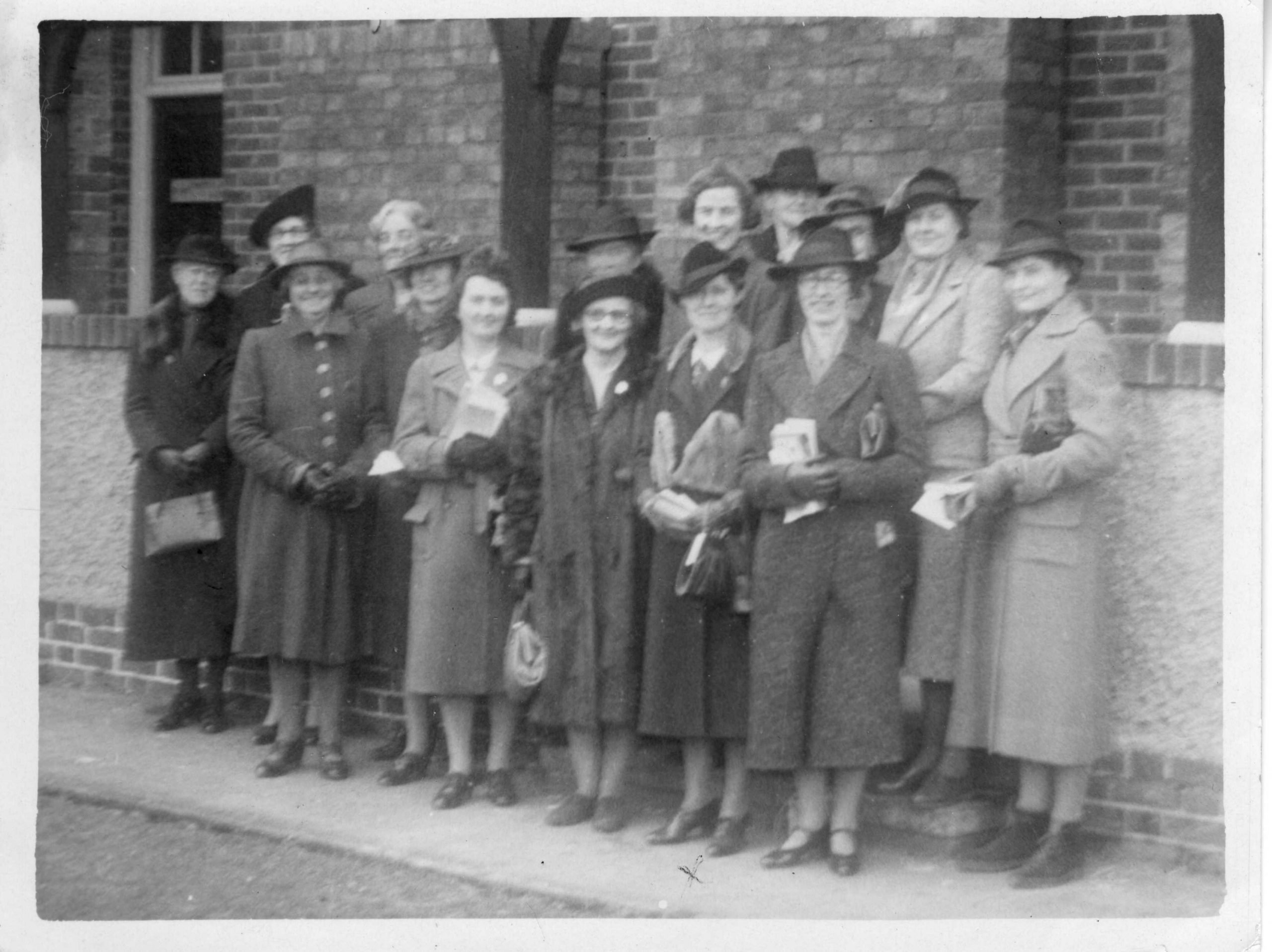 A black and white photograph of a group of women standing outside a train station